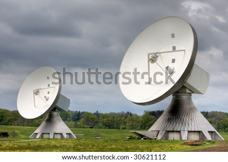Two earth station satellite installations  - the type used for broadcasting. Poor weather. - stock photo
