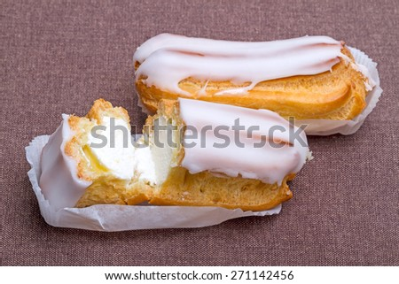 Two eclair cake on brown cloth - stock photo