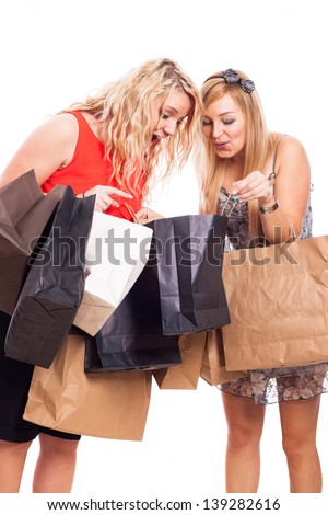 Two ecstatic blond girls looking into shopping bags, isolated on white background - stock photo