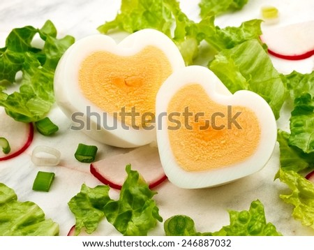Two egg hearts with salad, close up - stock photo