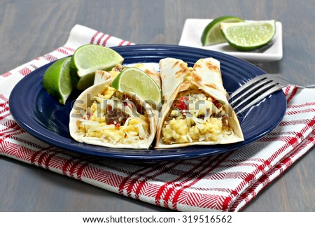 Two egg, sausage, pepper, onion and cheese breakfast tacos. - stock photo