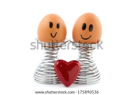 two eggs in egg holder with heart symbol in front of it isolated - stock photo
