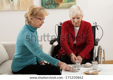 Two elder women drinking coffee and spending time together - stock photo