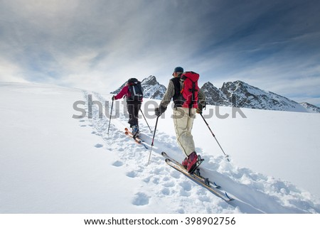Two elderly alpine skiers climb on skis and sealskins - stock photo
