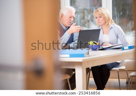 Two elderly colleagues talking about business cases - stock photo