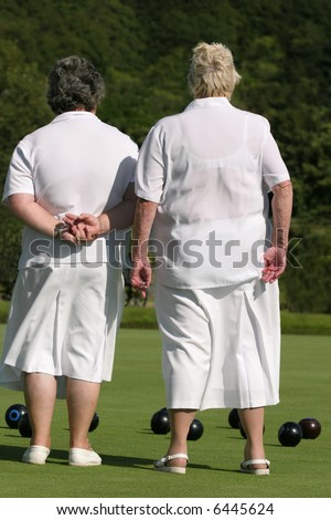 Two elderly ladies dressed in white outfits,  standing together on a lawn bowling green. Rear view. - stock photo