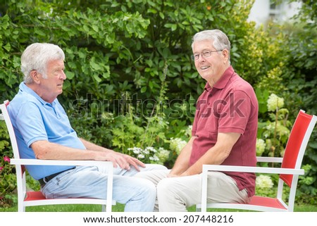 Two elderly men are sitting and enjoying the time together - from the side - stock photo