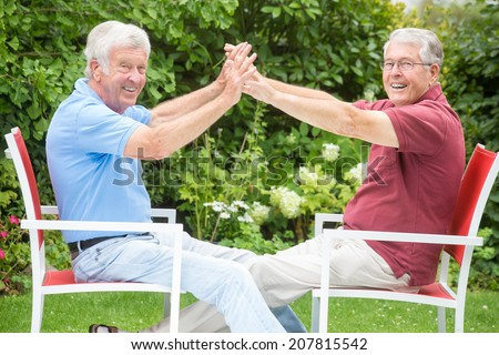 Two elderly men are touching each others arms and are having a great time - close to each other and both looking into the camera - stock photo