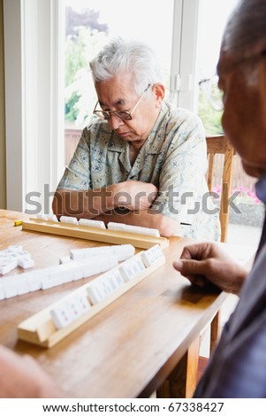 Two elderly men sitting at table playing game - stock photo