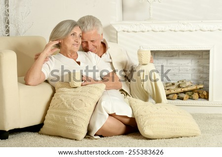Two elderly people sitting at home on couch - stock photo