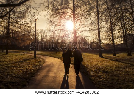 Two elderly people walking in a park in the sunset - stock photo