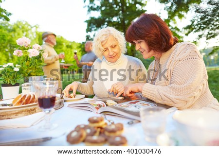 Two elderly women reading cookbook while eating cake in a garden - stock photo
