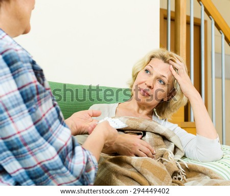 Two elderly women with pill on couch indoor  - stock photo