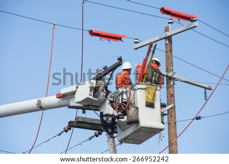 Two electric power workers hover in a bucket as they make repairs. - stock photo