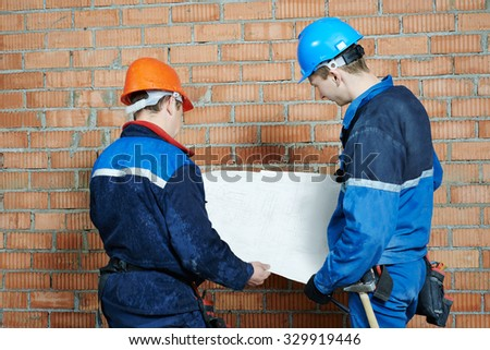 two electrician builder engineer with blue print scheme project indoors during cabling - stock photo