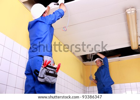 Two electrician inspection ceiling panels - stock photo