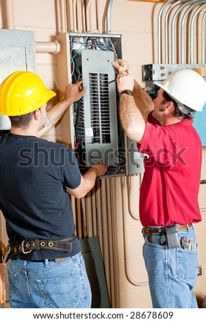 Two electricians repairing an electrical circuit breaker panel in an industrial setting. - stock photo