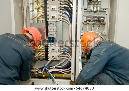 Two electricians working on a industrial panel mounting and assembling new wiring - stock photo