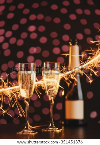 Two elegant champagne glasses and bottle with sparkler, focus on first glass