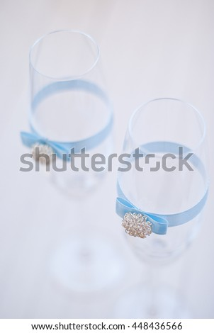 Two elegant champagne glasses with decoration ribbon.White background.Shallow depth of field - stock photo