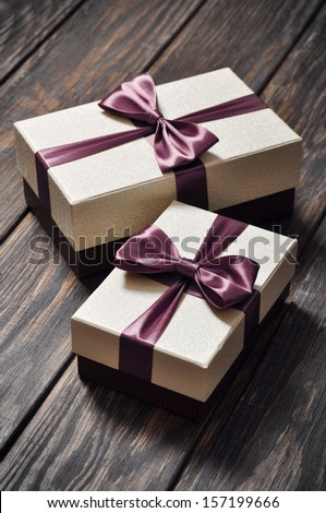 two elegant gift boxes on a wooden background - stock photo