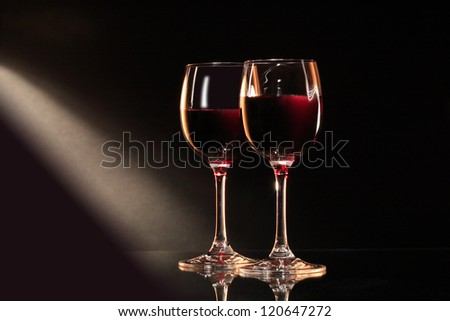 Two elegant goblets of red dry wine on dark background
