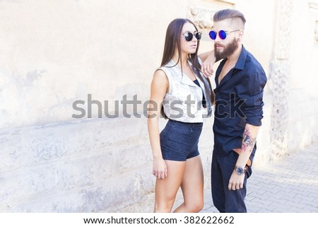 Two elegant hipster people in sunglasses posing.