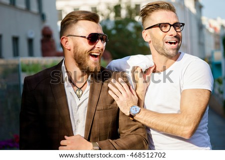 Two elegant smiling bearded men on street background