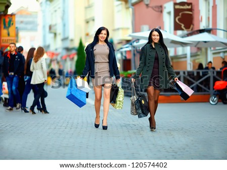 two elegant women shopping in the city stores