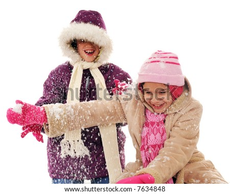 Two elementary girls having fun in the snow. - stock photo