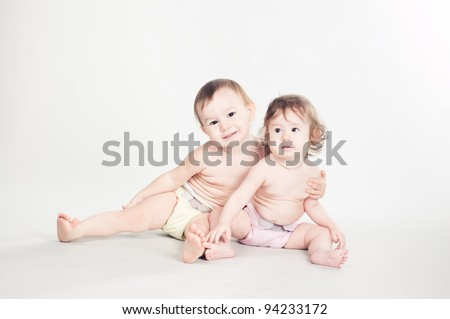 Two embracing siblings  sitting on the floor, isolated on white