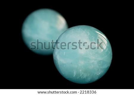 Two emerald green zen stress balls, isolated over a black background. Originated from China, these balls are to be rolled around in the palm of one hand. - stock photo