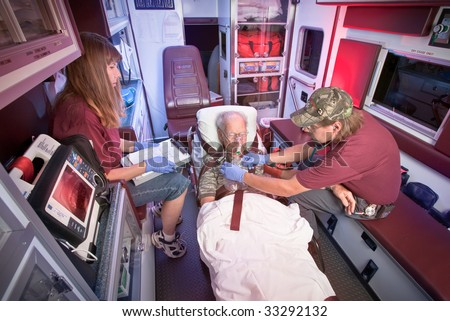 Two Emergency Medical Technicians treat an older patient inside the ambulance. - stock photo