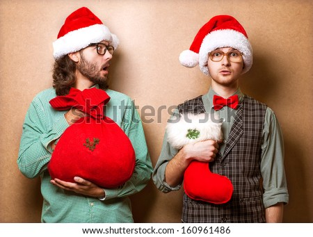 Two emotional Santa Claus  dressed in clothes hipster with the bag of the presents - stock photo