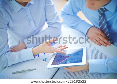 Two employees discussing business document in touchpad at meeting