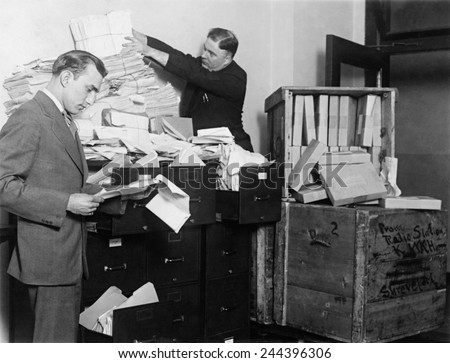 Two employees of the Federal Radio Commission overwhelmed by piles of mail in 1929. Federal Radio Commission was established in 1926 to end chaos caused by broadcasters competition for radio waves. - stock photo