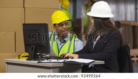 Two employees working together in shipping warehouse - stock photo
