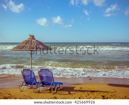 Two empty beach chair with umbrella on blue sea - stock photo