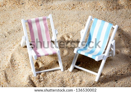 two empty chairs on a beach - stock photo