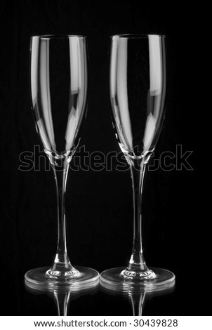 Two empty champagne flutes with mirror reflection on black background