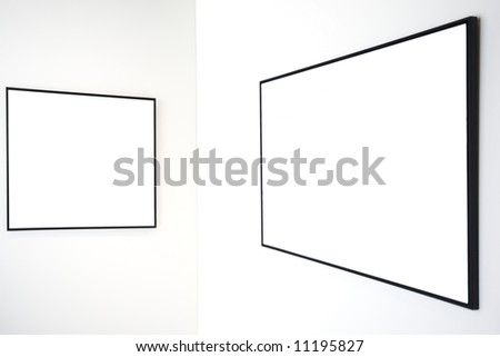 Two empty frames on white wall in museum - stock photo