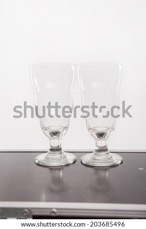 Two empty glasses for cocktails standing on the bar - stock photo