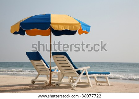 Two empty lounge chairs on the beach - stock photo