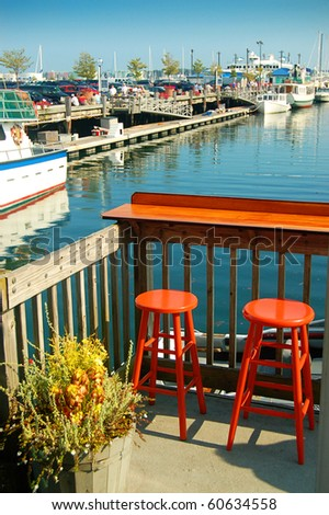 Two Empty Orange Bar Stools Overlooking Maine Harbor - stock photo