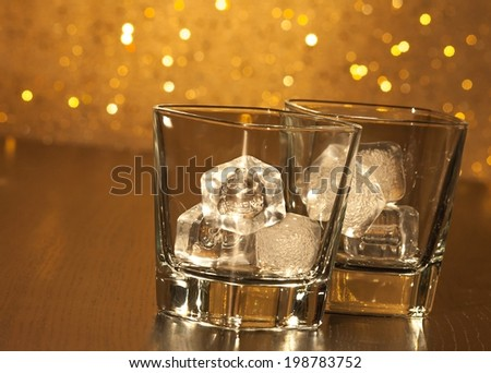 two empty whiskey glasses on wood table and gold bokeh background