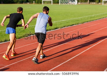 Two energetic men jogging outdoors on sunny day