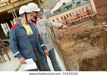 Two engineer builders with blueprint at construction site - stock photo