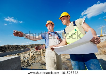 Two engineer builders with blueprint plan at construction site - stock photo