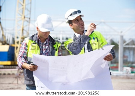 Two engineers at construction site are inspecting works on site according to design drawings. - stock photo