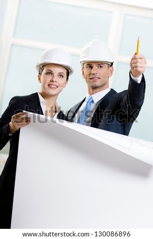 Two engineers discuss their cooperation keeping blueprint - stock photo